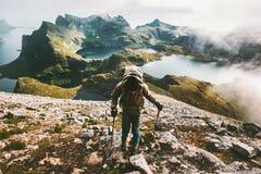 Hombre del viajero que sube al top de la montaña de Hermannsdalstinden en Noruega Imágenes de archivo libres de regalías