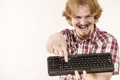 Hombre del videojugador que sostiene el teclado de ordenador Foto de archivo libre de regalías