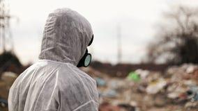 Hombre del virólogo en careta antigás protectora del traje y del respirador que camina cerca de la contaminación del vertedero, d metrajes