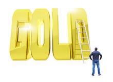 Hombre delante de la palabra de oro enorme ORO con una escalera Foto de archivo libre de regalías