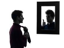 Hombre delante de su espejo que viste para arriba la silueta foto de archivo libre de regalías