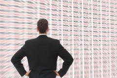 Hombre delante de una pantalla grande con números Foto de archivo libre de regalías