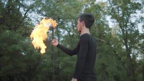 Hombre delgado joven en ropa negra y máscara que realiza una demostración con la situación de la llama en riverbank Artista exper metrajes