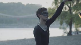 Hombre delgado joven en ropa negra y máscara que realiza una demostración con la situación de la llama en riverbank Artista exper almacen de video