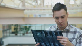 Hombre dentro de las miradas de la oficina hechas a la imagen de las radiografías de la espina dorsal almacen de video