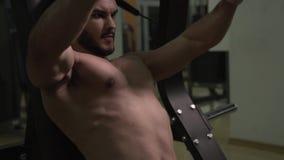 Hombre deportivo atlético con el torso desnudo que se resuelve en el ejercicio de la máquina