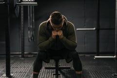 Hombre deportivo fuerte que se sienta en avería del sufrimiento del banco del gimnasio para superar imagen de archivo