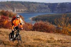 Hombre deportivo joven con la mochila roja que monta una bicicleta debajo del río con el fondo de la naturaleza Imagen de archivo libre de regalías