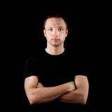 Hombre deportivo joven en camiseta negra en negro Imagen de archivo libre de regalías