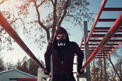 Hombre deportivo joven en la máscara que trabaja al aire libre Foto de archivo