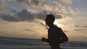 Hombre deportivo joven que corre en la playa del mar en la puesta del sol Individuo atlético que activa a lo largo de orilla del  Fotografía de archivo libre de regalías