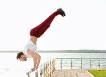 Hombre deportivo joven que hace ejercicios acrobáticos Imagen de archivo libre de regalías