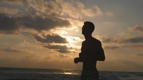 Hombre deportivo joven que salta antes de correr en la playa del mar en la puesta del sol Calentamiento atlético del individuo en