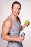 Hombre deportivo joven que sostiene una botella de agua Foto de archivo