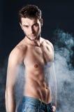 Hombre deportivo joven sobre humo imagenes de archivo