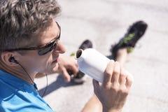 Hombre deportivo que escucha la música durante el entrenamiento Fotografía de archivo libre de regalías