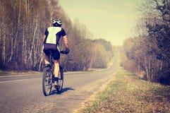 Hombre deportivo que monta una bicicleta en el camino Imagen de archivo libre de regalías