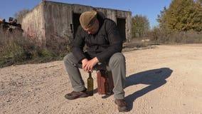 Hombre deprimido con la botella de vino que se sienta en la maleta almacen de metraje de vídeo