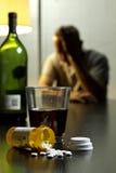 Hombre deprimido con las píldoras del vino y de la prescripción, verticales Imágenes de archivo libres de regalías