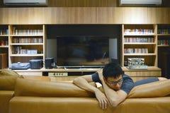 Hombre deprimido delante de la TV en sala de estar en la noche fotografía de archivo libre de regalías