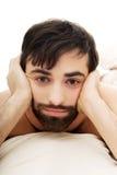 Hombre deprimido en dormitorio Foto de archivo libre de regalías