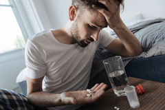 Hombre deprimido infeliz que mira su palma Imagen de archivo libre de regalías