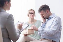 Hombre deprimido que llora durante la sesión de terapia imagen de archivo libre de regalías