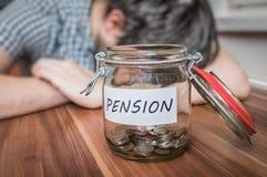 Hombre deprimido que miente en la tabla Ahorros de la pensión en tarro en frente fotografía de archivo libre de regalías