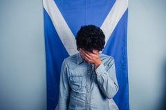 Hombre deprimido que se coloca delante de bandera escocesa Foto de archivo