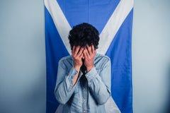 Hombre deprimido que se coloca delante de bandera escocesa Fotografía de archivo