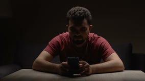 Hombre deprimido que se sienta en sitio vacío oscuro con el smartphone, para llamada que espera almacen de video