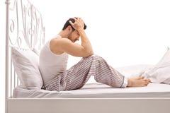Hombre deprimido que se sienta en una cama con su cabeza abajo Foto de archivo libre de regalías