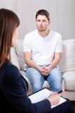 Hombre deprimido sicopático en visita psiquiátrica Foto de archivo