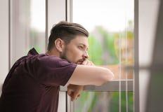 Hombre deprimido solo cerca de la ventana fotografía de archivo
