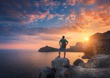 Hombre derecho joven con la mochila en la piedra en la puesta del sol Foto de archivo libre de regalías