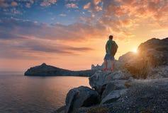 Hombre derecho joven con la mochila en la piedra en la puesta del sol Fotos de archivo libres de regalías