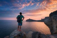 Hombre derecho joven con la mochila en la piedra en la puesta del sol Foto de archivo