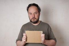 Hombre desaliñado que lleva a cabo la muestra Foto de archivo