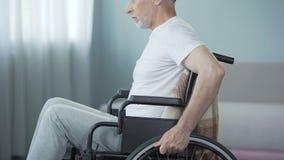 Hombre desamparado con las incapacidades que se sientan en la silla de ruedas, dando vuelta de nuevo a cámara metrajes