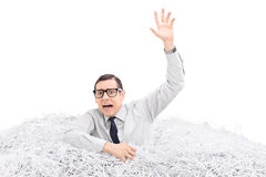 Hombre desamparado que se ahoga en una pila de papel destrozado imágenes de archivo libres de regalías