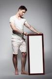 Hombre descalzo que exhibe al tablero blanco con el balneario en blanco Imagen de archivo libre de regalías
