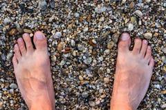 Hombre descalzo que se coloca en Rocky Beach Imagenes de archivo