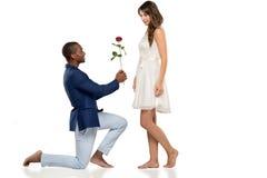 Hombre descalzo romántico que propone a su amor Foto de archivo