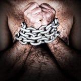 Hombre descamisado con sus manos encadenadas Fotografía de archivo