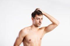 Hombre descamisado de la aptitud que se sostiene el pelo Tiro del estudio foto de archivo