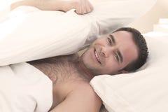 Hombre descamisado en cama y la sonrisa Imágenes de archivo libres de regalías