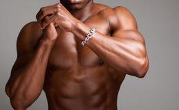 Hombre descamisado muscular con las manos abrochadas Foto de archivo libre de regalías