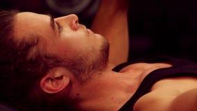 Hombre descamisado que ejercita con pesas de gimnasia almacen de video
