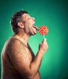 Hombre descamisado que lame el caramelo Foto de archivo