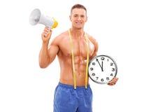 Hombre descamisado que sostiene un reloj y un megáfono Fotos de archivo libres de regalías